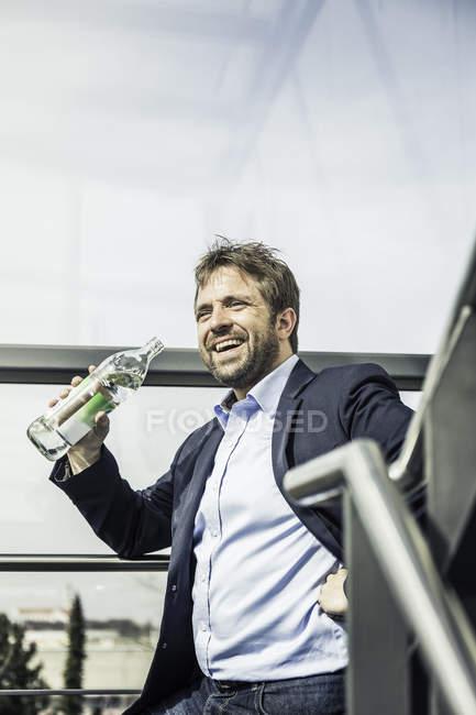 Бізнесмен питної води в пляшках на офісні сходи і посміхається — стокове фото