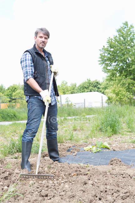 Portrait of organic farmer raking soil — Stock Photo