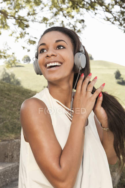 Happy young woman listening to music on headphones — Stock Photo
