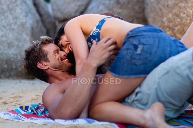 Пара объятий на пляжном полотенце — стоковое фото