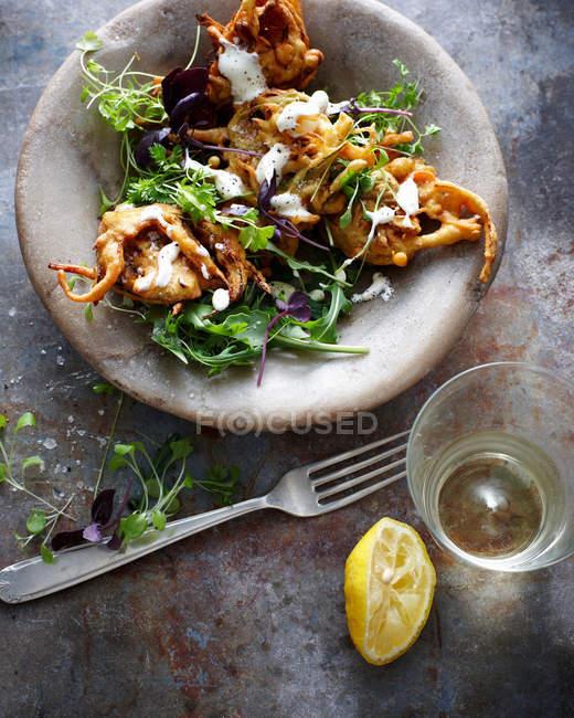 Placa de carne con ensalada y yogur servido sobre mesa con vaso y limón - foto de stock