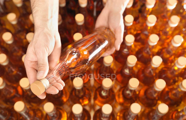 Factory worker examining bottle in plant, close-up partial view — Stock Photo