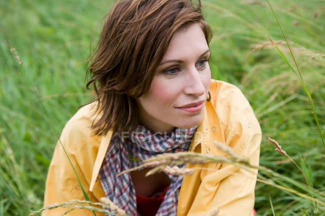 Улыбающаяся женщина сидит в высокой траве — стоковое фото