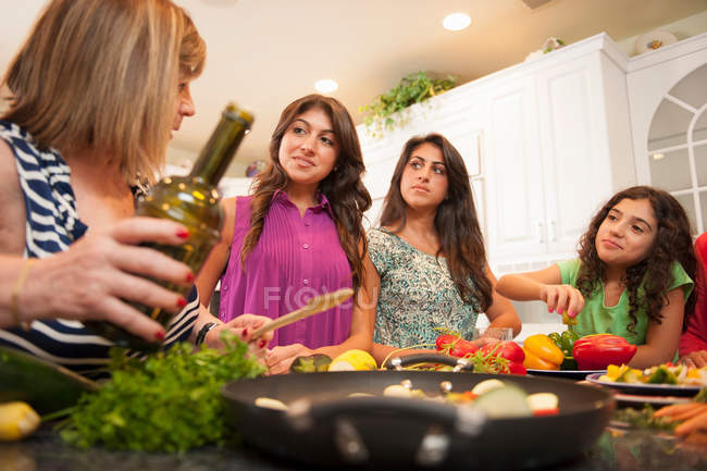 Women cooking together in kitchen — Stock Photo