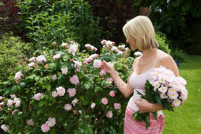 Woman looking at roses in garden — Stock Photo