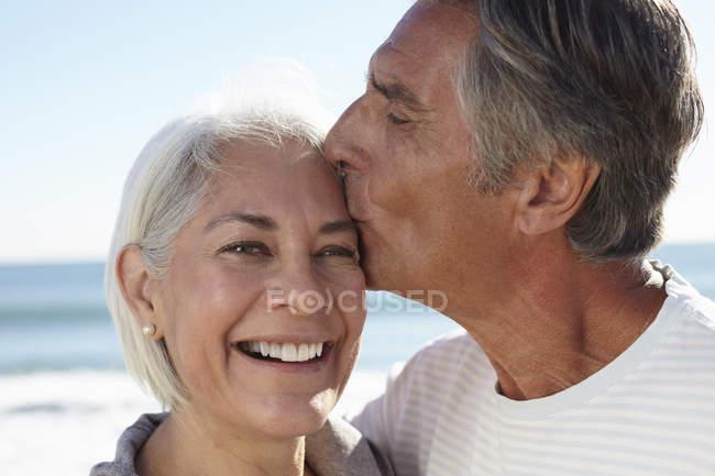 Mann küsst Frau auf die Stirn — Stockfoto