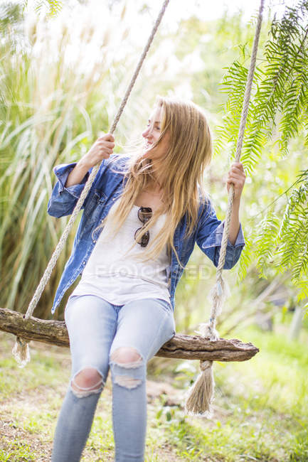 Happy young woman swinging on garden swing — Stock Photo