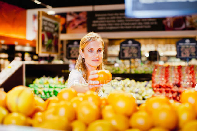 Woman choosing orange in grocery store — Stockfoto