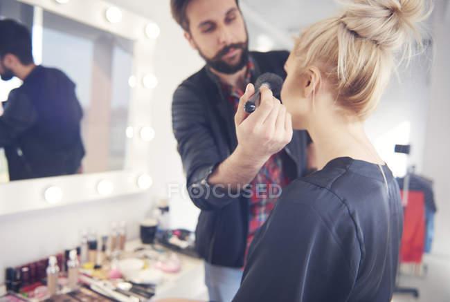 Männliche Visagistin trägt Blusher auf Model für Fotoshooting auf — Stockfoto