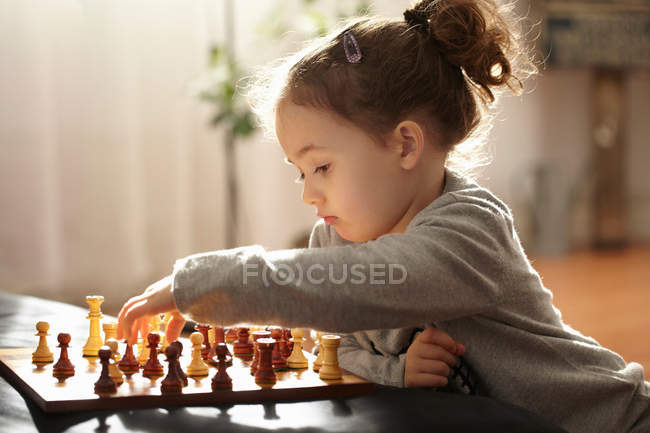 Girl playing chess indoors, selective focus — Stock Photo