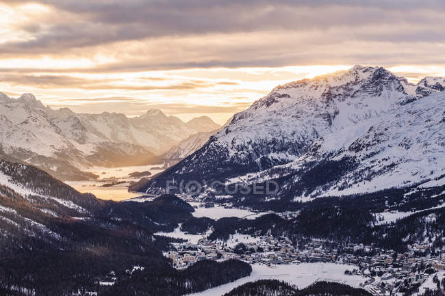 Snowcapped rocky mountains under cloudy sunset sky — Stock Photo