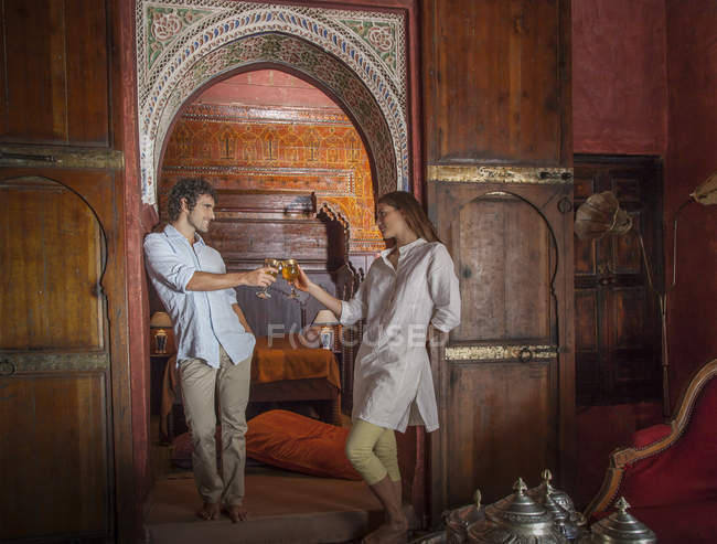 Young couple in riad making a toast in archway, Marrakesh, Morocco — Stock Photo
