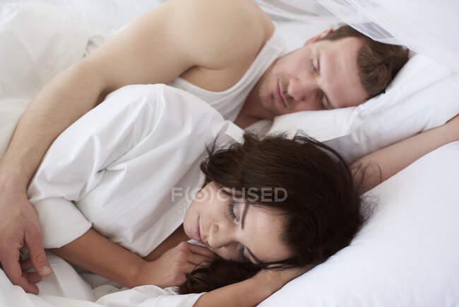 Молоде подружжя спить разом у ліжку. — стокове фото
