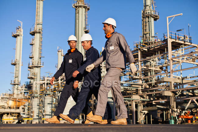 Workers walking at oil refinery — Stock Photo