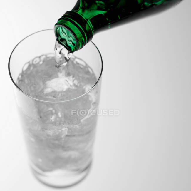 Pouring sparkling water into glass — Stock Photo