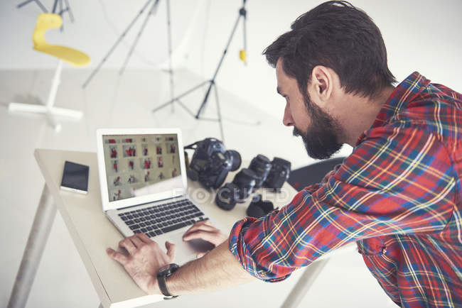Male photographer  reviewing photo shoot on laptop in studio — Stock Photo