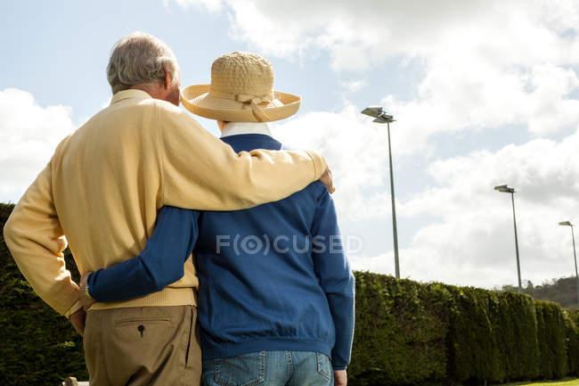 Vista trasera del esposo y la esposa mirando cobertura - foto de stock