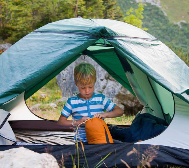 Menino desembalar saco de dormir na barraca — Fotografia de Stock
