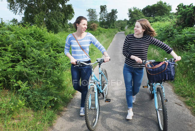 Two young adults pushing bicycles and chatting along country lane — Stock Photo