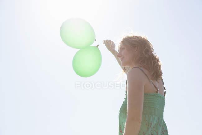 Жінка тримає два зелений повітряних куль, Уельс, Великобританія — стокове фото