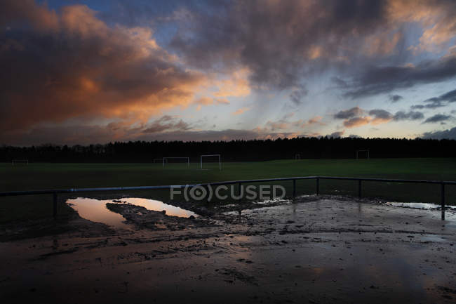 Terrain de football au crépuscule avec ciel dramatique — Photo de stock