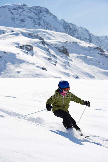 Child skiing on snowy mountainside — стоковое фото