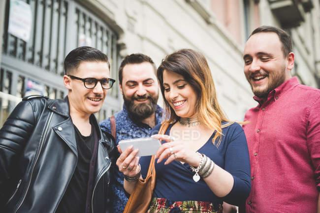 Група друзів дивлячись на повідомлення на стільниковий телефон разом — стокове фото