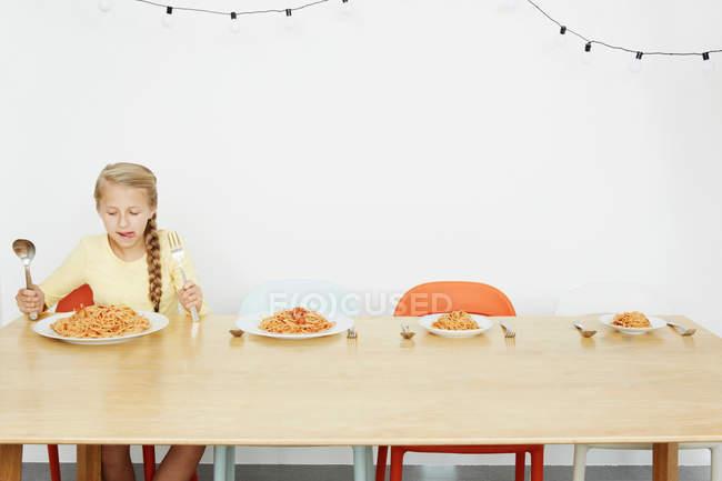 Jeune fille assise à table avec spaghetti et trois plaques plus — Photo de stock