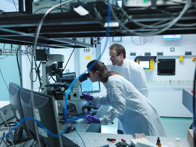 Ученые в лаборатории, используя микроскоп — стоковое фото