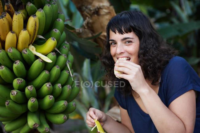 Mujer comiendo plátano recogido fresco y sonriente - foto de stock