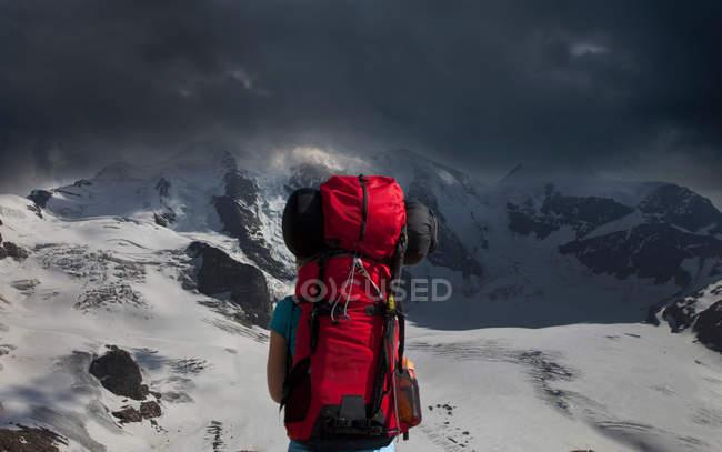 Заднього виду fackpacker, милуючись бурхлива гори — стокове фото
