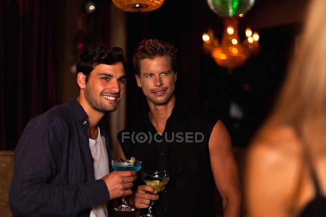 Uomini sorridenti che bevono cocktail nel club — Foto stock
