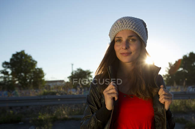 Portrait of young woman in leather jacket and beanie — Stock Photo
