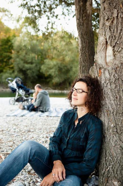 Madre che riposa sull'albero lontano dalla famiglia — Foto stock