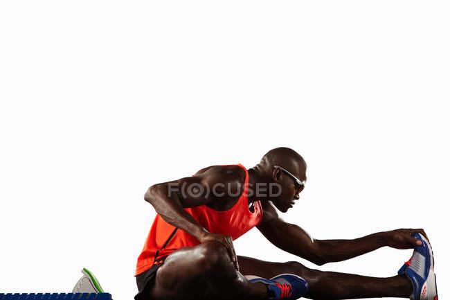 Runner stretching at starting line — Stock Photo