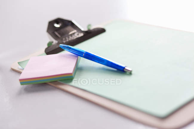 Clipboard with note papers and pen on table — Stock Photo
