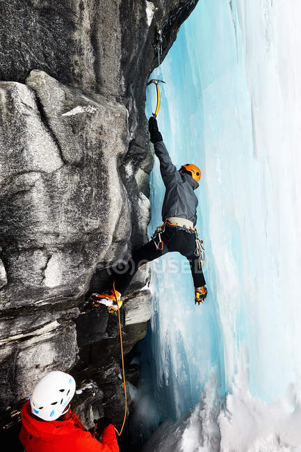 Ice climbers climbing on rock face — Stock Photo