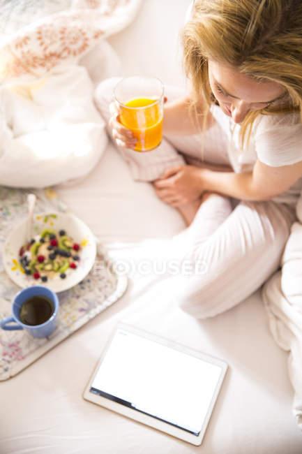 Draufsicht der jungen Frau auf Bett und Las digital-Tablette morgens — Stockfoto