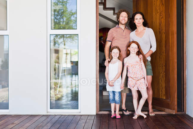 Family smiling at front door — Stock Photo