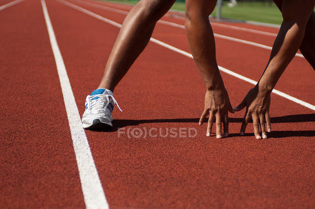 Close up partial view of young athlete in start position — Stock Photo
