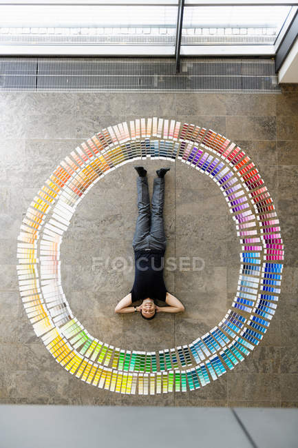 Businessman laying with paint swatches — Stock Photo