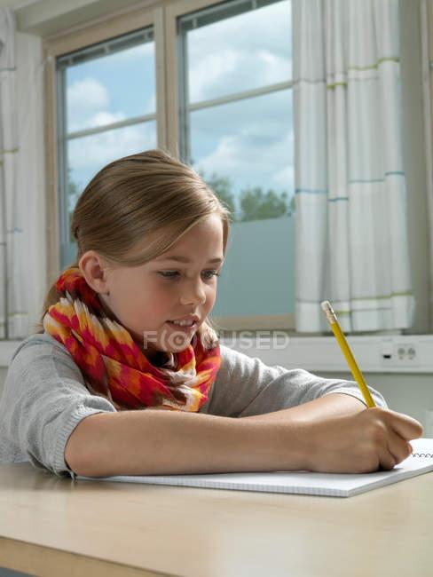 Дівчина писати в botebook з олівцем у класі — стокове фото