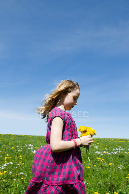 Girl carrying wildflowers in field — Stock Photo