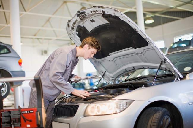 Meccanico esaminando motore auto in garage — Foto stock