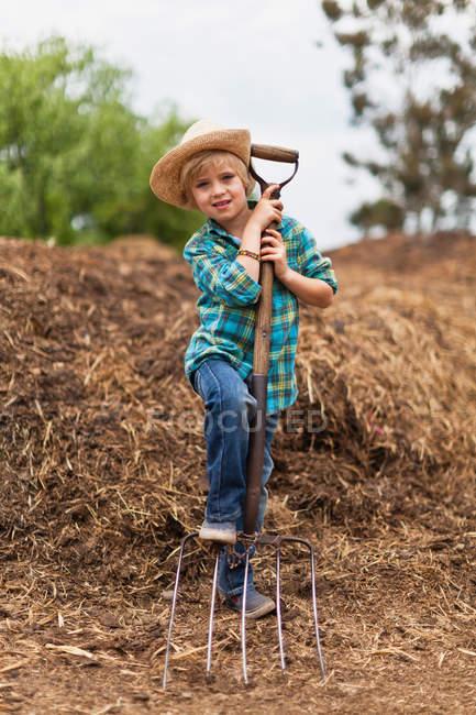 Мальчик использует вилы в стоге сена, избирательный фокус — стоковое фото