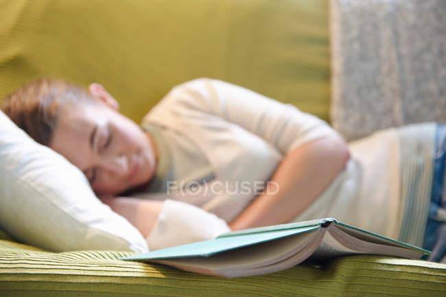 Giovane donna sdraiata sul divano, con libro — Foto stock
