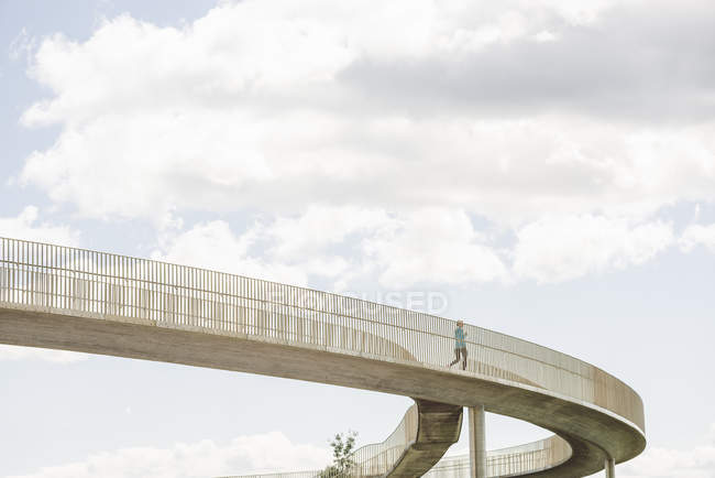 Low angle view of female runner crossing footbridge — Stock Photo