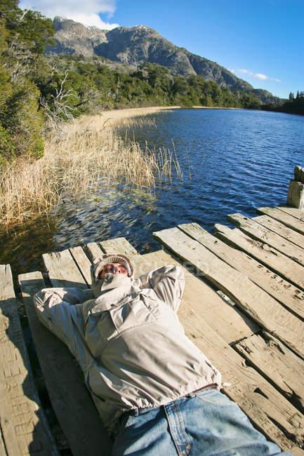 Людини, лежачи на лаві підсудних у озера — стокове фото