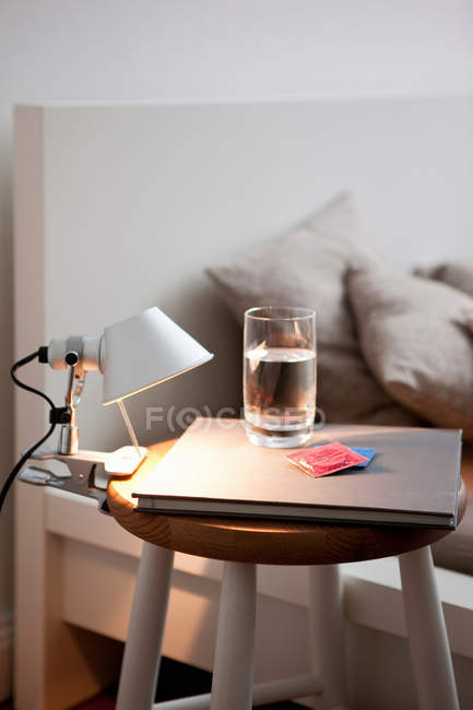 Preservativos e água na mesa de cabeceira, close-up vista — Fotografia de Stock
