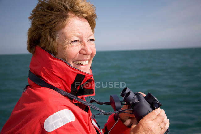Woman with binoculars by ocean — Stock Photo